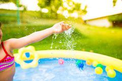Unrecognizable girl having fun in the garden swimming pool Stock Photos