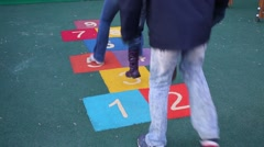 Family of three jumps after each other playing hopscotch together. Stock Footage