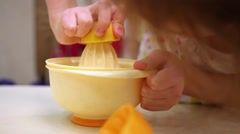 Little girl squeezes fresh juice from lemons on table in kitchen. Stock Footage