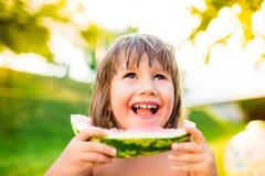 Cute little girl eating watermelon in sunny summer garden Stock Photos