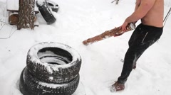 Bare-chested guy beats stack of tires with wooden club at sportsground Stock Footage