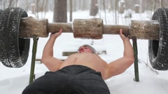 Bare-chested guy lies at lounger and pushes up wooden barbell Stock Footage
