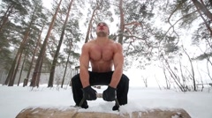 Bare-chested guy lifts, pushes up and lowers wooden heavy load Stock Footage
