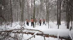 Eight people runs through the thickets and climb over fallen tree Stock Footage