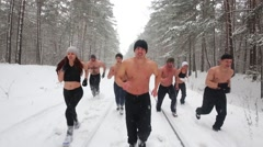 Group of eight bare-chested young people runs along snowy railway Stock Footage