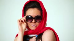 Girl model in red-white head kerchief and dark sunglasses. - stock footage