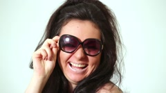 Dark-haired laughing girl model in dark sunglasses poses at studio. Stock Footage
