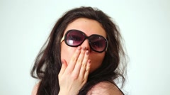 Dark-haired laughing girl model in dark sunglasses gives air kiss. Stock Footage