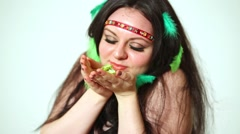 Dark-haired girl model with feathers in hair holds petals. Stock Footage