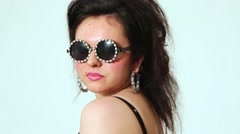 Dark-haired girl model in dark round sunglasses with strasses turns posing Stock Footage