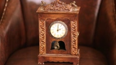 Small wooden clock with swinging pendulum on leather armchair. Stock Footage