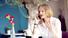 Unhappy businesswoman quarrelling through cellphone in the cafe Stock Footage