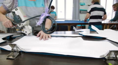 Tailor cutting the patterns with electric saw - stock footage