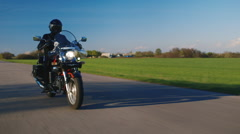 Motorcycle riding on a background of green field and blue sky Stock Footage