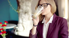 Businesswoman drinking coffee and improving her jacket in the cafe Stock Footage