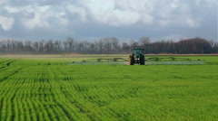 green tractor spraying the wheat field with chemicals in cloudy spring day - stock footage