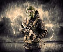 Dangerous armed terrorist with mask and gun in a thunderstorm with lightning - stock photo