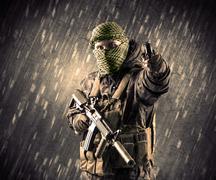 Armed terrorist man with mask on rainy background - stock photo