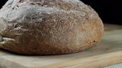 A loaf of black bread on wooden cutting board Stock Footage
