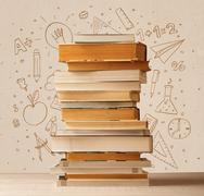 A pile of books on table with school hand drawn doodle sketches - stock photo