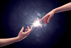 Hands reaching to light a spark - stock photo