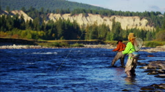 Male female rod and reel fly fishing in freshwater river Stock Footage