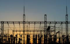 High voltage power tower and silhouette power lines sunset. - stock photo