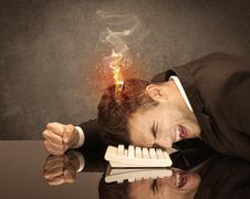 Stock Photo of Sad business person's head catching fire