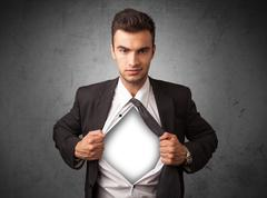Businessman tearing off his shirt with white copyspace on chest - stock photo
