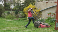 Little boy playing with a lawn mower in the garden - stock footage