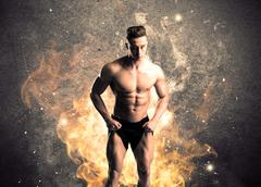 Healthy hot male showing muscles with fire - stock photo
