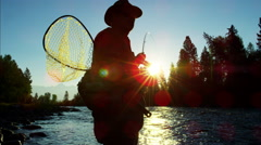 Sunrise silhouette of man fishing for Cutthroat Trout in freshwater river Stock Footage