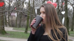 Beautiful young urban fashion woman in autumn park smiling and drinkging Stock Footage