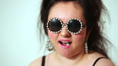 Girl model in dark round sunglasses with strasses chews gum posing Stock Footage