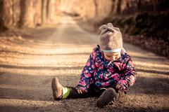 Little baby toddler sitting and playing on road in winter - stock photo