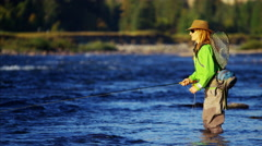 Rod and reel female casting line in freshwater river sunrise USA Stock Footage