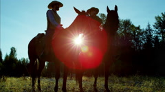 Sunset silhouette of working ranch hands riding horses in forest valley Canada Stock Footage