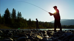 Rod and reel fisherman in silhouette casting line in freshwater river USA Stock Footage