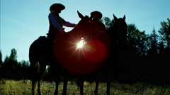 Sunrise silhouette of working ranch hands riding horses in forest valley Canada Stock Footage