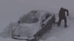 Man digging up stuck in snow car Stock Footage