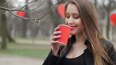 Portrait of beautiful young urban fashion girl in autumn park drinking cup of Stock Footage