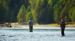 Fisherman using rod and reel fly fishing in freshwater river USA Stock Footage
