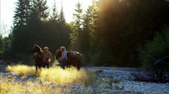 Riders with horses in forest valley Rocky mountains USA Stock Footage