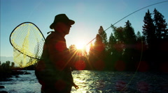 Sunrise silhouette of fisherman fly fishing outdoor in freshwater river - stock footage