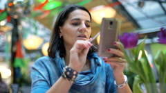 Woman browsing internet on smartphone and talking to someone, steadycam shot Stock Footage