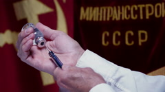 COMMUNIST DOCTOR FILLS SYRINGE FROM AN INJECTION BOTTLE. Stock Footage
