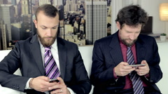 Two business men with beard sitting on couch texting message with smartphone. Stock Footage