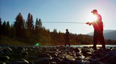 Sunrise silhouette rod and reel fishermen casting line in freshwater river USA Stock Footage