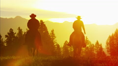 Silhouette reveal of Cowboy Riders in sunset wilderness Canada Stock Footage