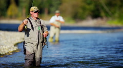 Fisherman using rod and reel casting line in freshwater river Canada Stock Footage